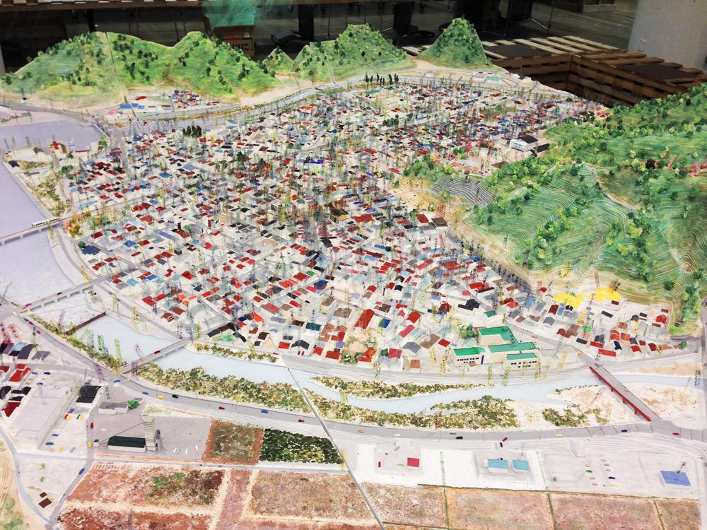 震災前の街を模型で作り、現地の住人の話を聞きながら、色づけ、書き留めた記憶の旗を立てていくプロジェクト。